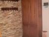 mediterrán házban kőberakással körbe vett cseresznyefa szekrény és fogas